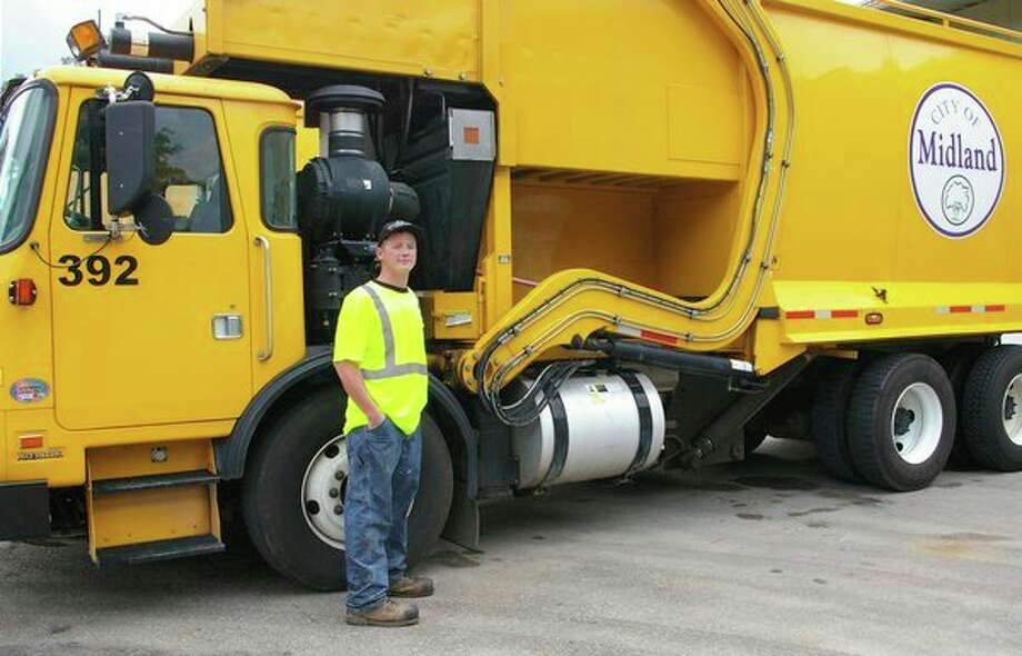 Alex Cross stands in front of the truck he drives for the City of Midland. He enjoys interacting with the residents he has met over the past year as a sanitation equipment operator. (Niky House/for the Daily News)