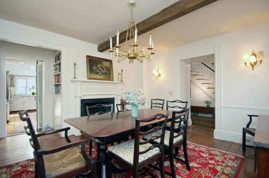 The formal dining room has chair railing, a fireplace, and exposed beam ceiling.