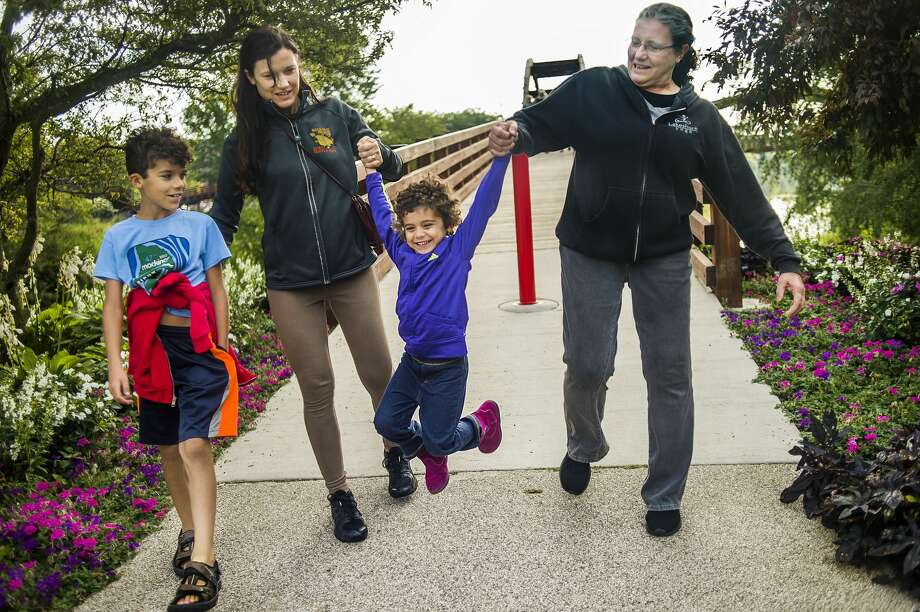 Ruth Tallman, right, and her daughter Karen Mendes, second from left, swing Mendes' daughter Annalisa, 3, in the air while Mendes' son Marcelo, 8, watches during the annual Labor Day Tridge Walk Monday, Sept. 2, 2019. (Katy Kildee/kkildee@mdn.net) Photo: (Katy Kildee/kkildee@mdn.net)