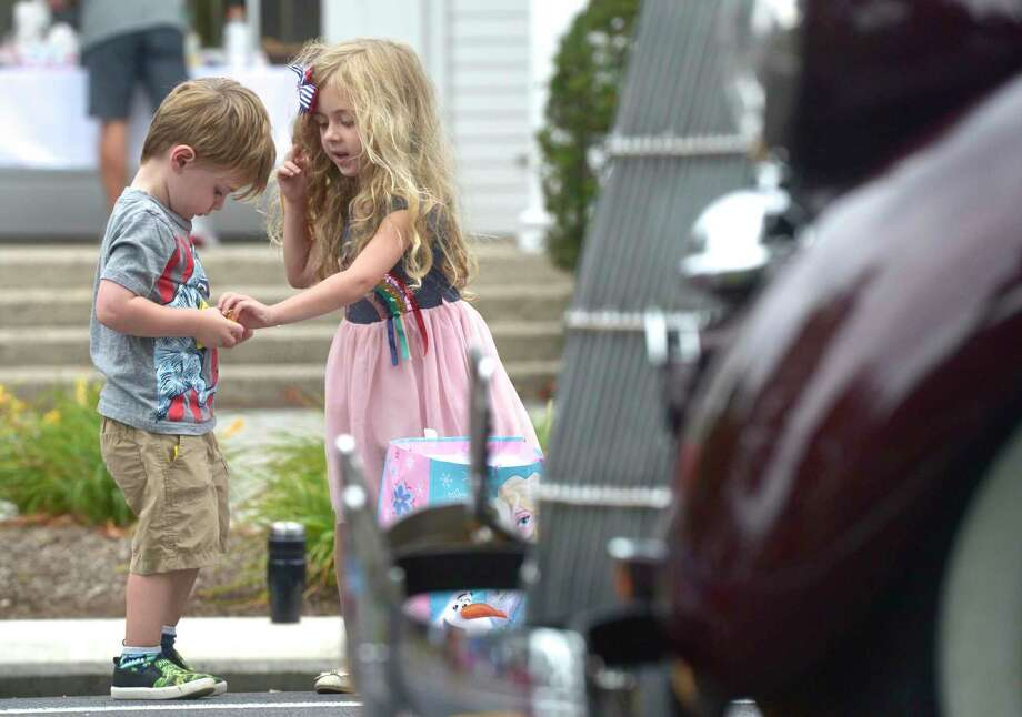Brother and sister Bobby, 3, and MacKenzie Loughran, 5, of Brookfield, collect candy along the route of the 2019 Newtown Labor Day Parade, Monday, September 2, 2019, in Newtown, Conn. Photo: H John Voorhees III / Hearst Connecticut Media / The News-Times