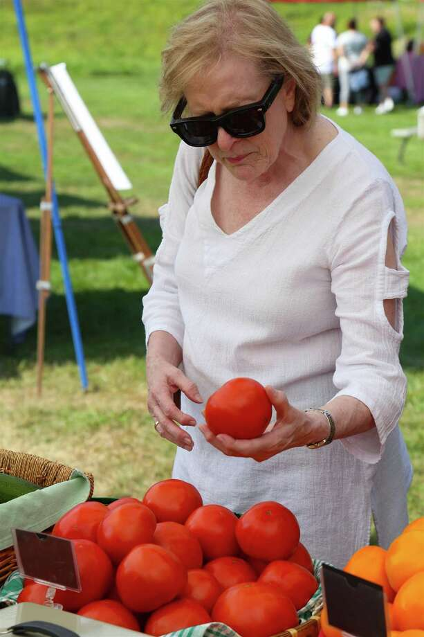 Jane Nottenburg of Norwalk checks out a tomato from Veronica's Garden of Ridgefield at the Lachat Farmer's Market on Friday, Aug. 30, 2019, at Lachat Town Farm in Weston, Conn. Photo: Jarret Liotta / Jarret Liotta / ©Jarret Liotta