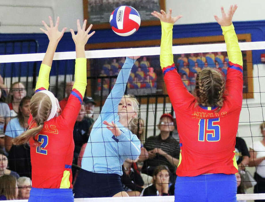 Jersey's Sally Hudson (middle) splits the block put up by Roxana's Reagen Stahlhut and Abbi Zangori (15) during a semifinal match in the Roxana Tourney on Saturday at Milazzo Gym. Photo: Greg Shashack / The Telegraph