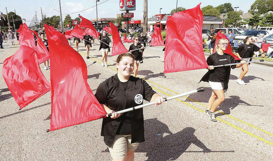 The Granite City High School Marching Warriors color guard twirl their flags Monday morning in the annual Labor Day Parade in Granite City. Hundreds turned out to watch the parade and politicians and gather candy by the handfuls.