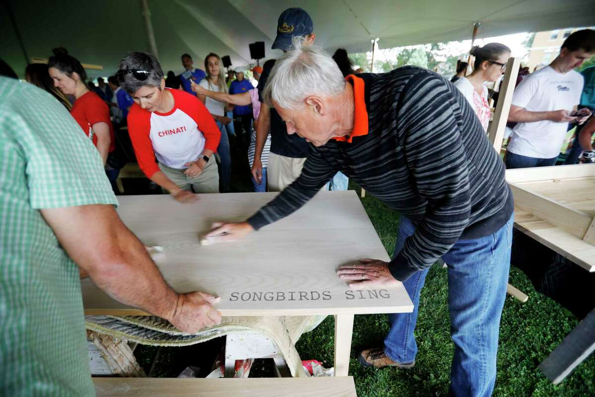 Hundreds of volunteers gather at The Common in Pittsfield, Mass., for a community Day of Action on Saturday, Aug. 10, 2019 to build wooden tables and benches with engravings inspired by the prompt: