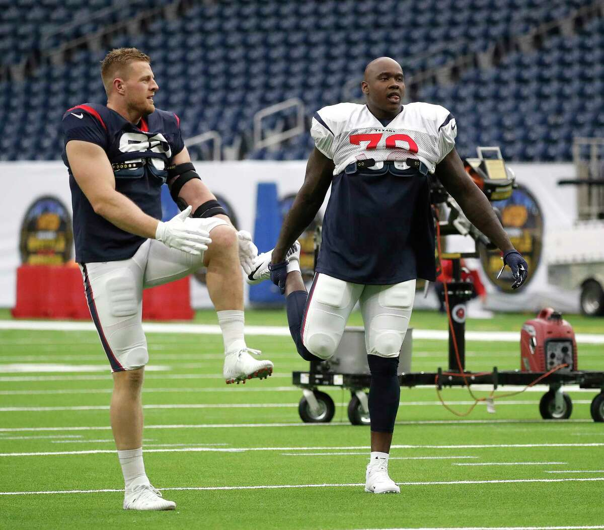 Newly acquired Texans left tackle Laremy Tunsil (78) stretches with defensive end J.J. Watt (99) during the Texans football practice at NRG Stadium, September 2, 2019, in Houston.