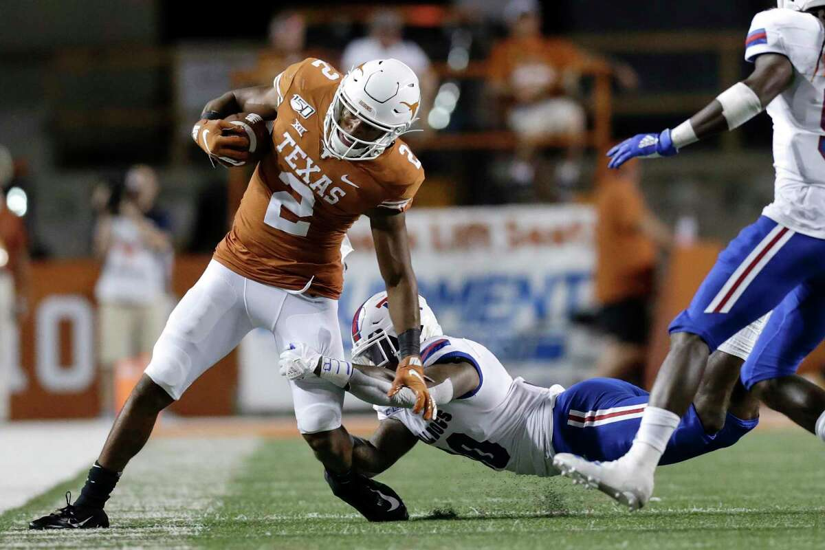 AUSTIN, TX - AUGUST 31: Roschon Johnson #2 of the Texas Longhorns runs the ball while defended by Aaron Roberson #30 of the Louisiana Tech Bulldogs in the fourth quarter at Darrell K Royal-Texas Memorial Stadium on August 31, 2019 in Austin, Texas. (Photo by Tim Warner/Getty Images)