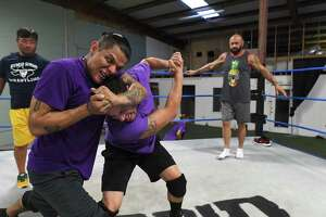 Richie Garcia has Branden Vice in a hold as Sho Funaki, left, and Rodney Mack watch and give advice at the Hybrid Wrestling school on Wednesday, Aug. 28, 2019.