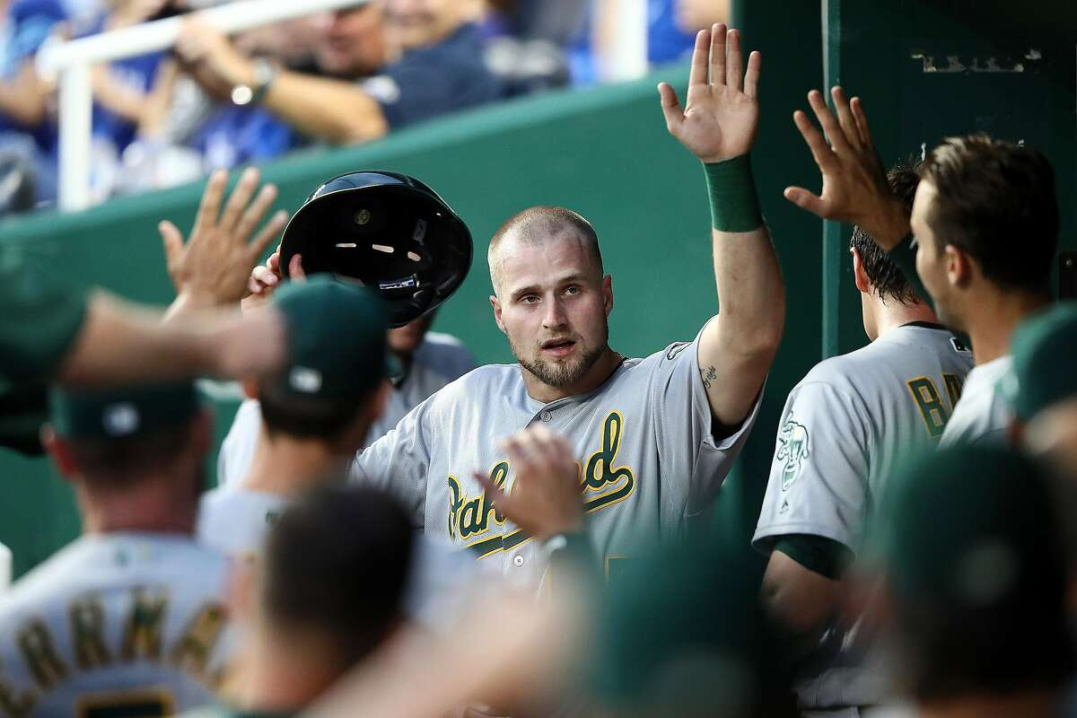 KANSAS CITY, MISSOURI - AUGUST 26: Seth Brown #65 of the Oakland Athletics is congratulated by teammates in the dugout after scoring during the 2nd inning of the game against the Kansas City Royals at Kauffman Stadium on August 26, 2019 in Kansas City, Missouri. (Photo by Jamie Squire/Getty Images)