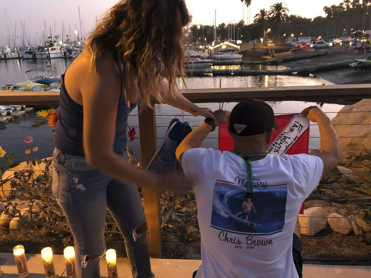 JJ Lambert, 38, and his fiancee, Jenna Marsala, 33, hang up a dive flag in remembrance of the victims of the Conception boat fire at a memorial site on Monday, Sept. 2, 2019, in Santa Barbara, Calif. A fire raged through the boat carrying recreational scuba divers anchored near an island off the Southern California coast early Monday, leaving multiple people dead and hope diminishing that any of the more than two dozen people still missing would be found alive. (AP Photo/Stefanie Dazio)