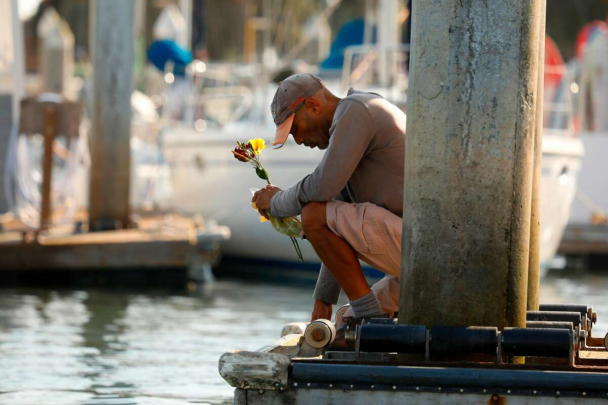 """At Santa Barbara Harbor near Sea Landing dock, James Miranda kneels in prayer for the victims of the boat fire on Sept. 2, 2019. """"I came here to bless them,"""" Miranda says. """"It's a very sad moment for California."""""""