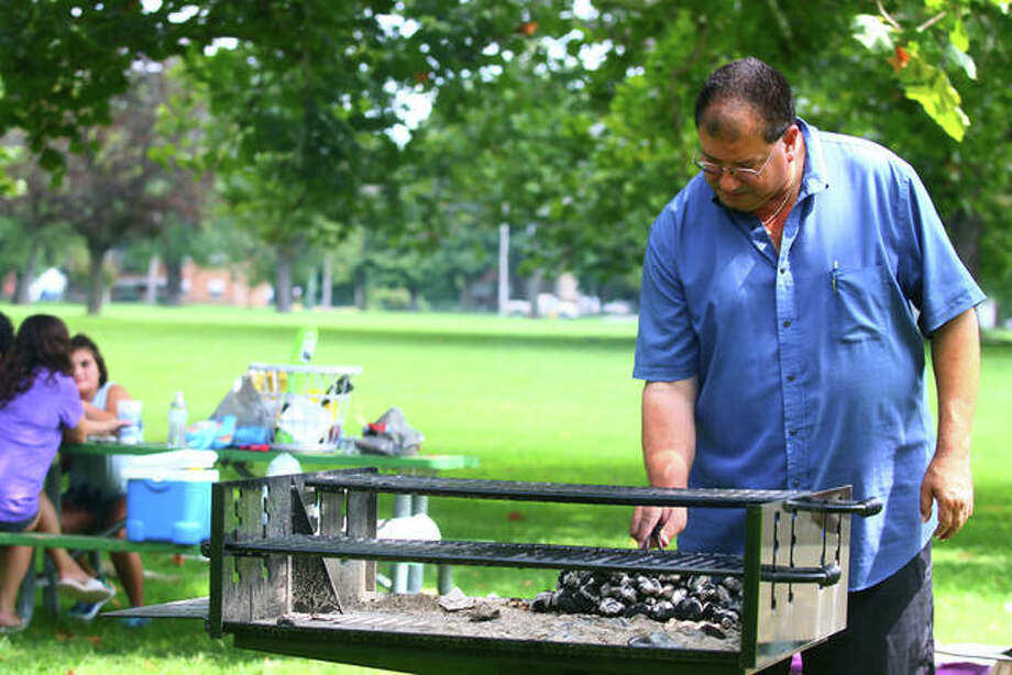 Peter Kokinias gets charcoal ready to grill out with his family at Community Park in Jacksonville, taking advantage of the pleasant weather on Monday's Labor Day holiday. Photo: Rosalind Essig | Journal-Courier