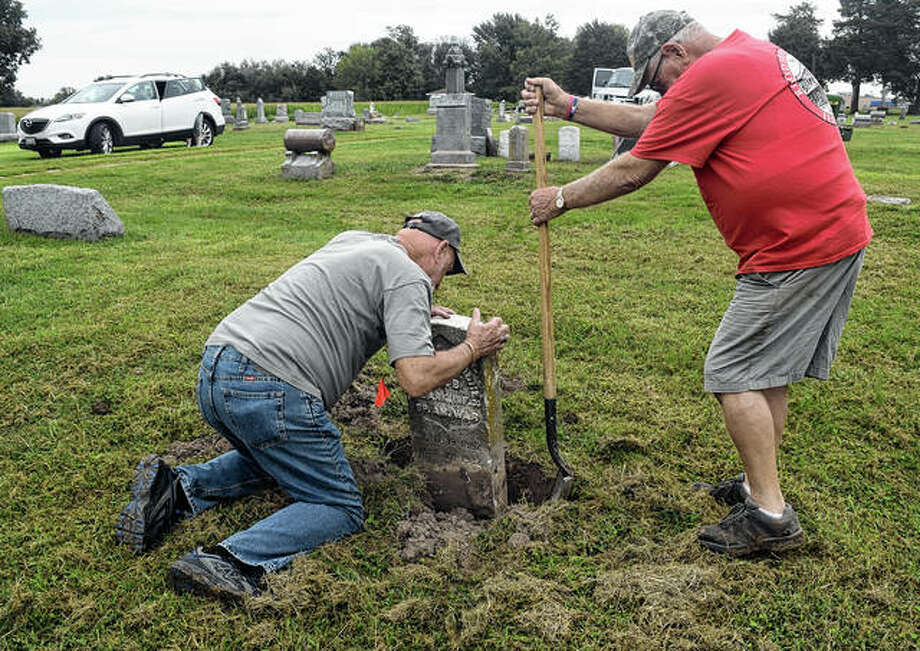 Dennis Cumby (from left) and Dick Roodhouse dig a tombstone at Fernwood Cemetery in Roodhouse. Roodhouse has led an effort to fix up old tombstones at Fernwood. About 70 headstones have already been cleaned up and set straight. Photo: Marco Cartolano | Journal-Courier