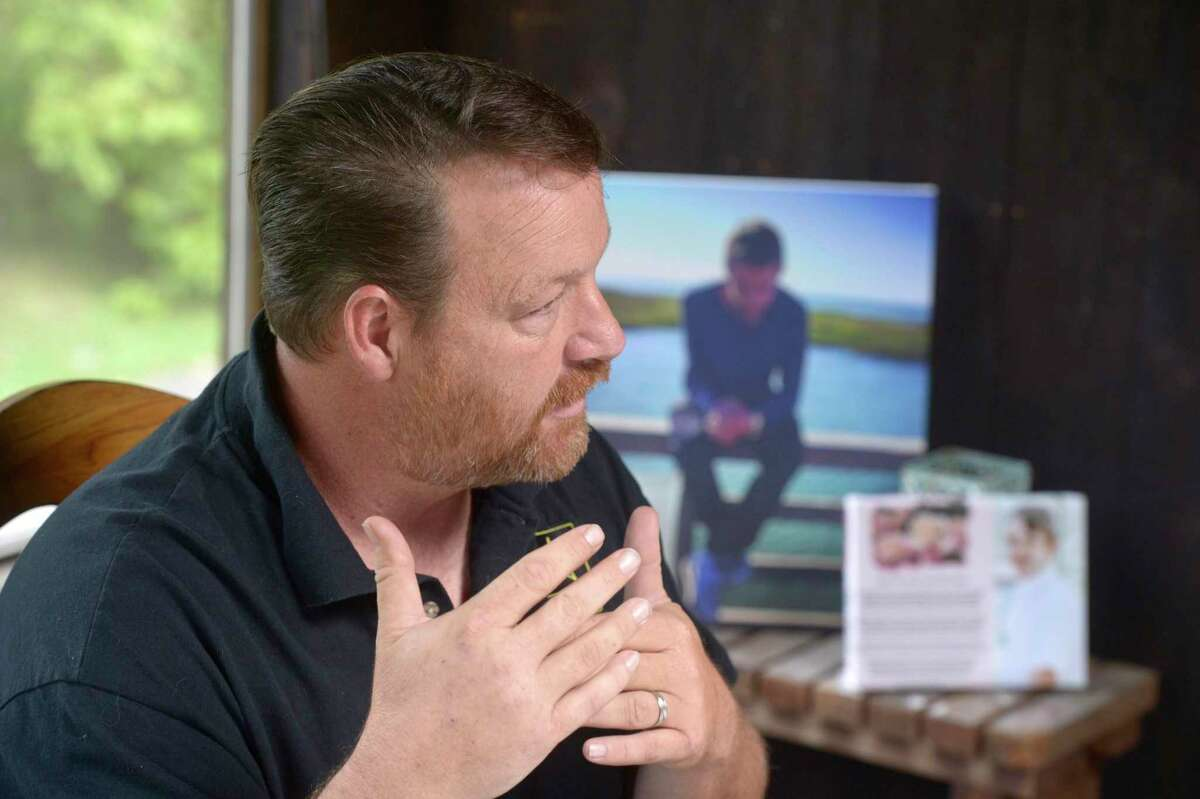 Tony Morrissey talks about his step-son Brian Cody Waldron who died from a drug overdose in August of 2019. Waldron's picture is displayed in the background. August 27, 2019, in New Milford, Conn.
