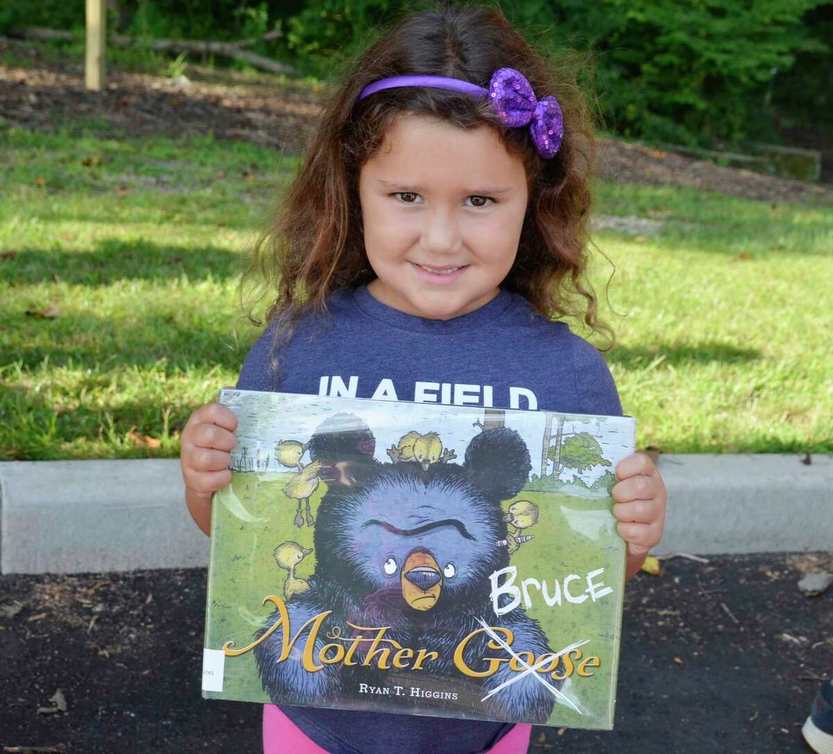 Olivia Valenzano holds up a copy of Mother Bruce by Ryan T. Higgins, which is the featured story at the first StoryWalk at Eisenhower Park. Library staff will change the story quarterly.