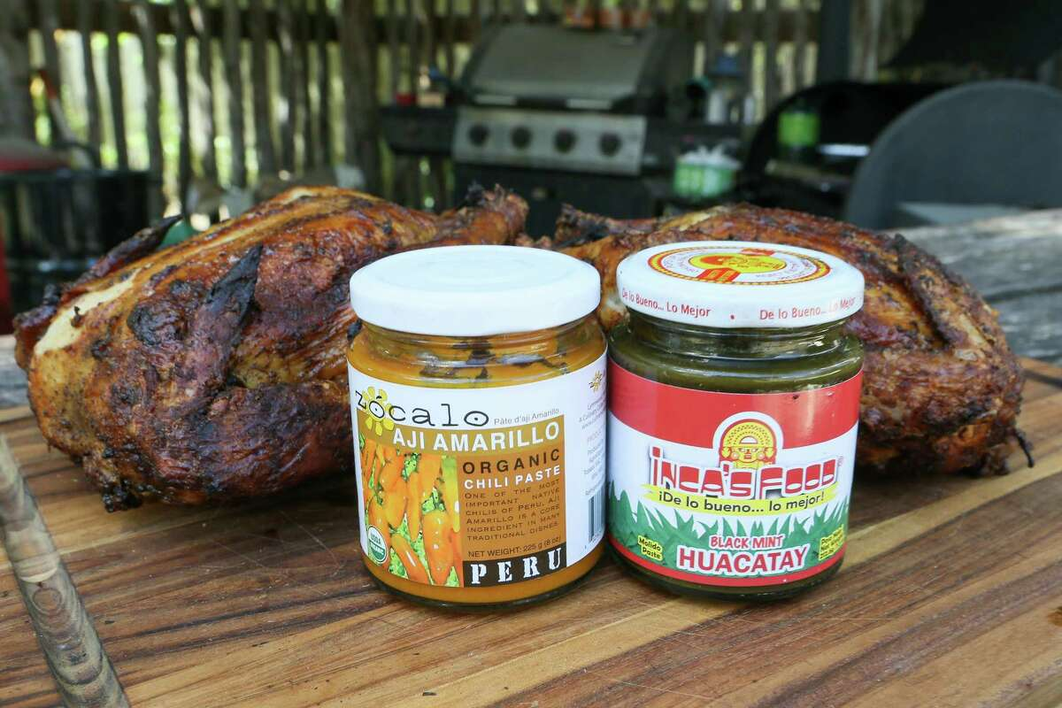 Aji amarillo, left, a chile paste made from the South American yellow pepper, and black mint huacatay, a popular Peruvian condiment, are used in preparing Peruvian-style chicken.