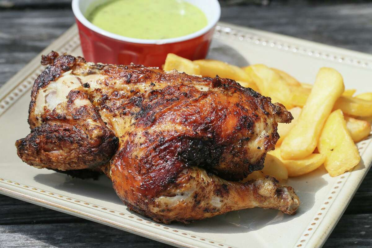 A finished Peruvian chicken half paired with traditional fries and a guacamole salsa for dipping.