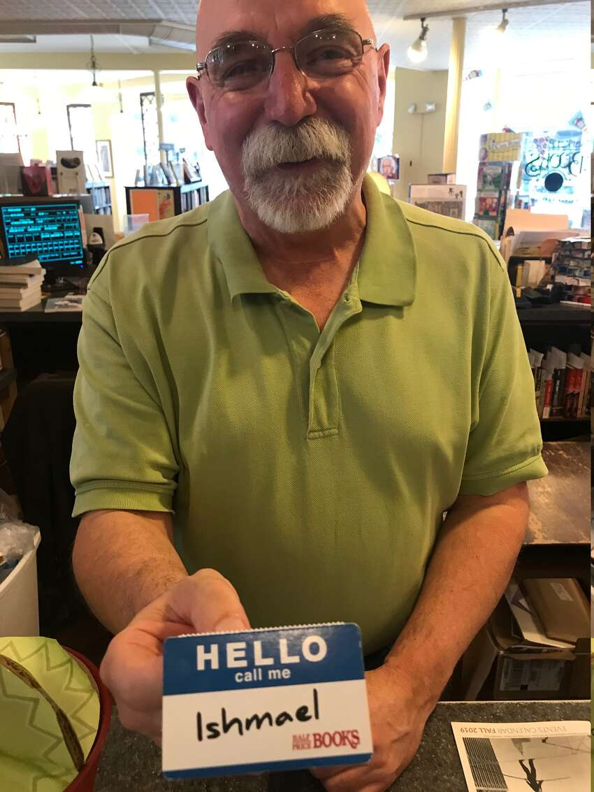 Stanley Hadsell with an Ishmael name tag a friend gave him, which he keeps next to his computer at Market Block Books in Troy (Paul Grondahl / Times Union)