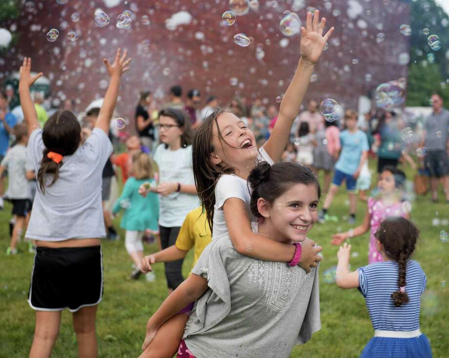 Allison Childs holds Isabella LaGravinese on her back as she reaches for bubbles on Friday, August 30, 2019 in Ridgefield, Connecticut at Barlow Mountain Elementary School. Parents hosted the school's annual Welcome Back Social celebration which featured the Bubble Bus. Photo: Hearst Connecticut Media / BryanHaeffele