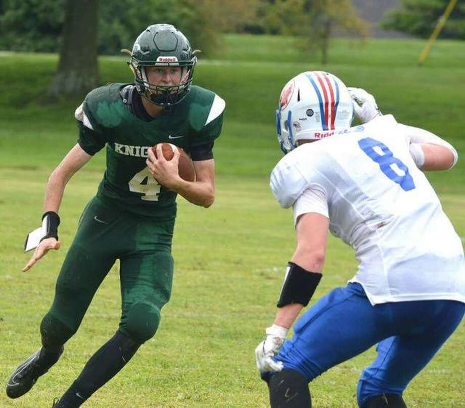 Metro-East Lutheran quarterback Zach Keplar, left, tries to get past a Rockford Christian Life defender during Saturday's game at MELHS.