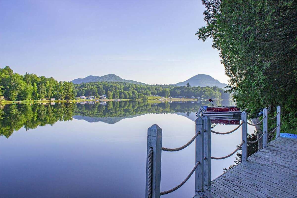 """Green Mountains: Eden, Vt. Lake View Manor. Price: $210. Sleeps nine. """"Jump off the dock to swim in the crystal clear water, fish in our rowboat or glide around the lake in our red canoe. Trails are everywhere, right outside your doorstep."""" View full listing on Airbnb."""