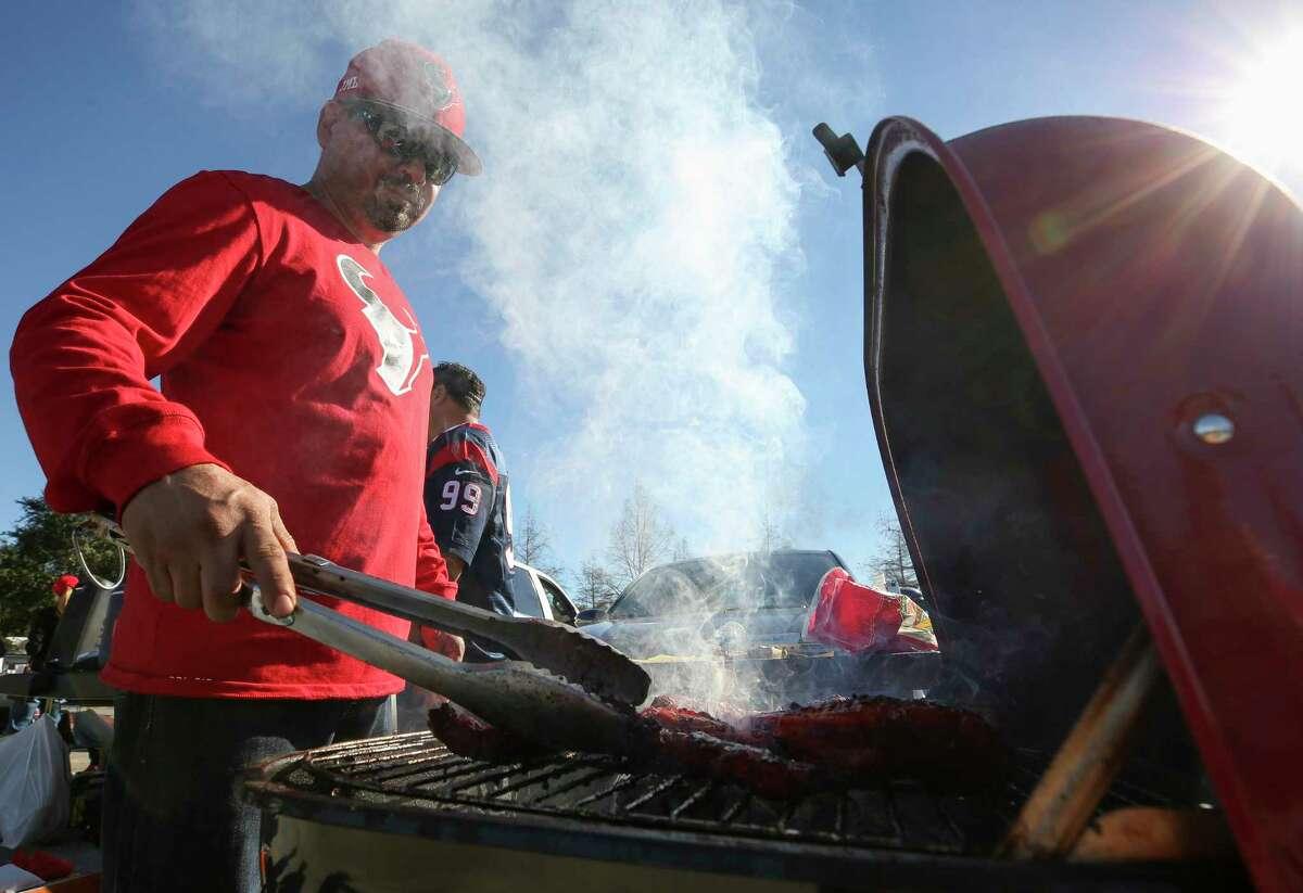 Juan Lara, 45, checks on the pork ribs while tailgating at NRG Stadium.