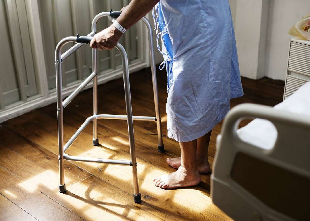 In this stock photo, an elderly woman is shown with a walker.