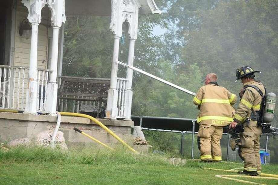 Firefighters adjust a ladder at a fire Tuesday on Sandusky Road. Photo: Samantha McDaniel-Ogletree | Journal-Courier