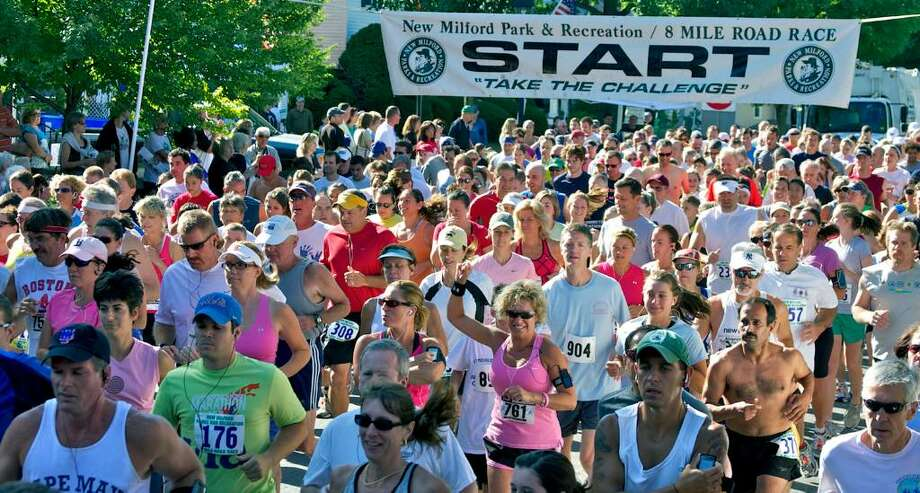 SPECTRUM/Kim Robles McMillen (761) of New Milford raises her fist as she joins nearly 700 other runners at the start of July 31, 2010's New Milford 8-mile road race and Village Fair Days 5K road races. Photo: Trish Haldin / The News-Times Freelance