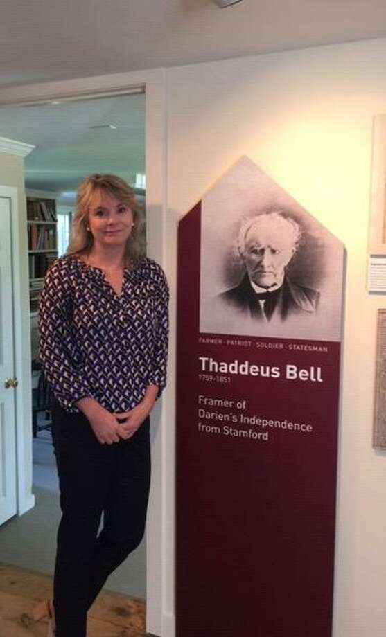 Maggie McIntire, executive director of the Darien Historical Society, stands next to a photo of Thaddeus Bell, one of Darien's founders Photo: Contributed Photo / / Connecticut Post