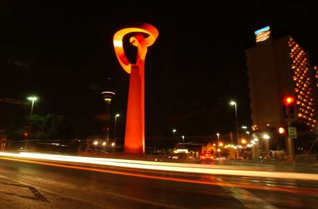 """Downtown traffic streaks past the """"Torch of Friendship"""" by Sebastian."""