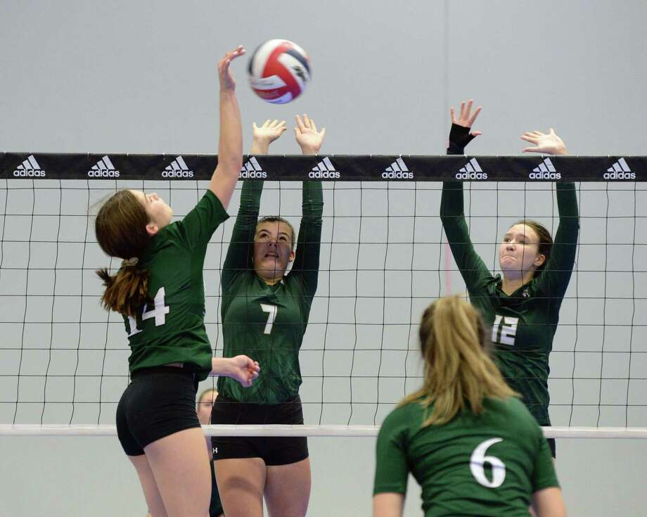 Chloe Ruzzo (7) and Fiona Charlton (12) of Awty attempt to block the shot of Jordan Booth (14) of Woodlands Christian during the first set of a volleyball match between the Awty International Rams and the Woodlands Christian Warriors on Friday, August 23, at Skyline Juniors, Houston, TX. Photo: Craig Moseley, Staff / Staff Photographer / ©2019 Houston Chronicle