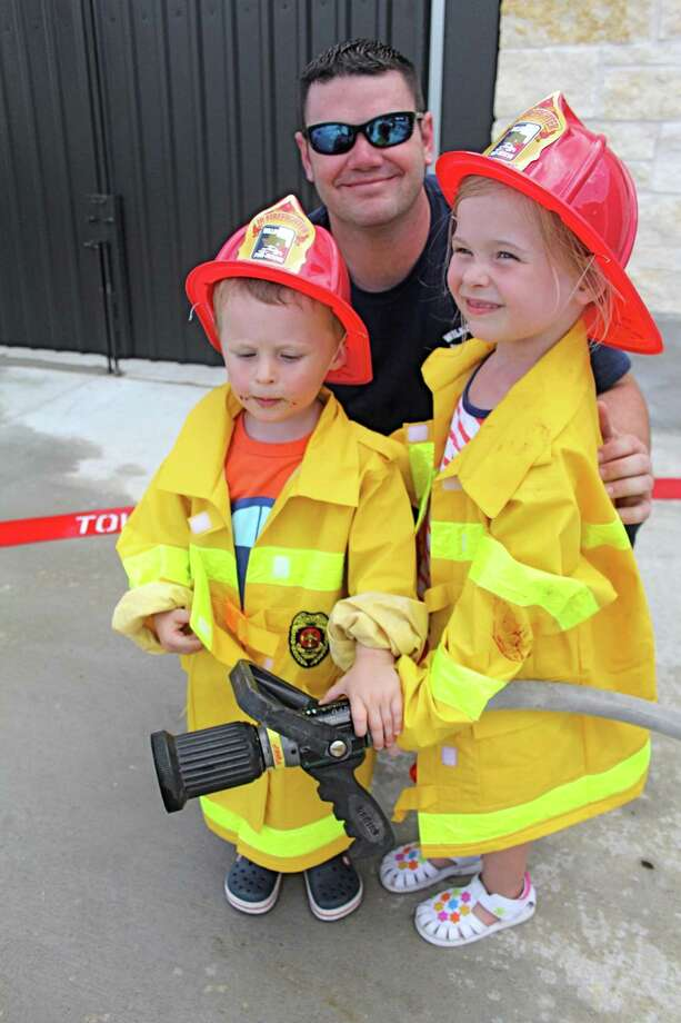 Willowfork Fire Station No. 2 firefighter Jarrett Ledget poses with Felix Smith, 2, and his sister, Bella Smith, 3. In conjunction with National Fire Safety Week, the Willowfork Fire Department will hold Open Houses at all three of its fire stations on Saturday, Oct. 12. Photo: Suzanne Rehak, Freelance Photographer / For The Chronicle