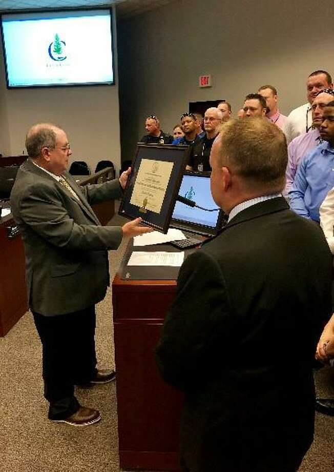 Huntsville Police Department Chief Kevin Lunsford presents the Conroe Police Departmentwith theTexas Police Chief's Association'sLaw Enforcement Agency Best Practices Recognition Program award last month at Conroe City Hall. Photo: Courtesy Of The Conroe Police Department
