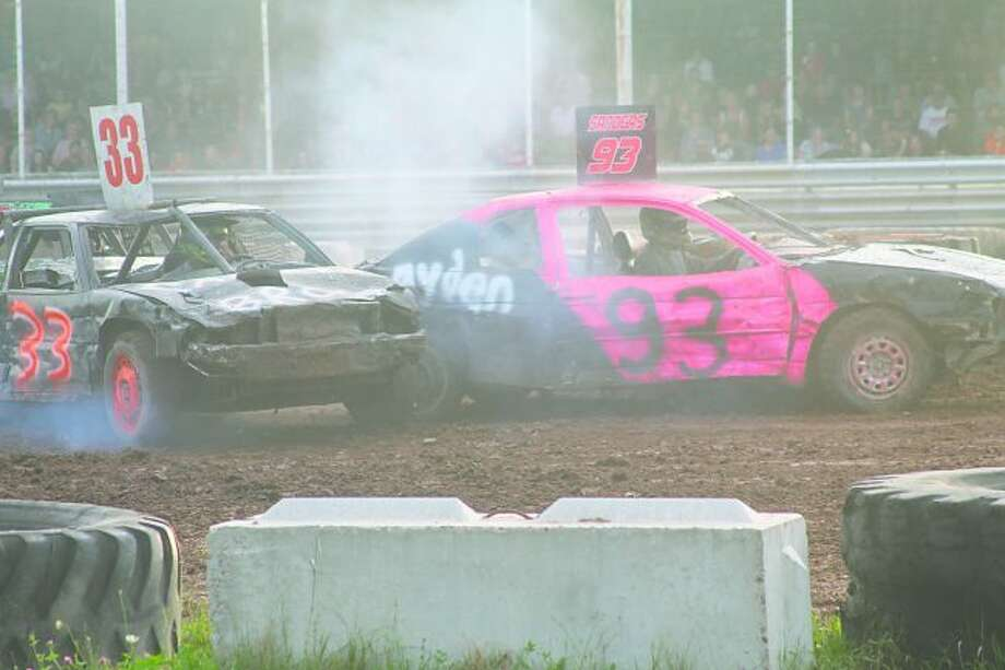 Demo Derby cars collide during a preliminary heat of the Manistee County Fair Figure-8 race in the Fairgrounds grandstand arena on Saturday. (Scott Fraley/News Advocate)
