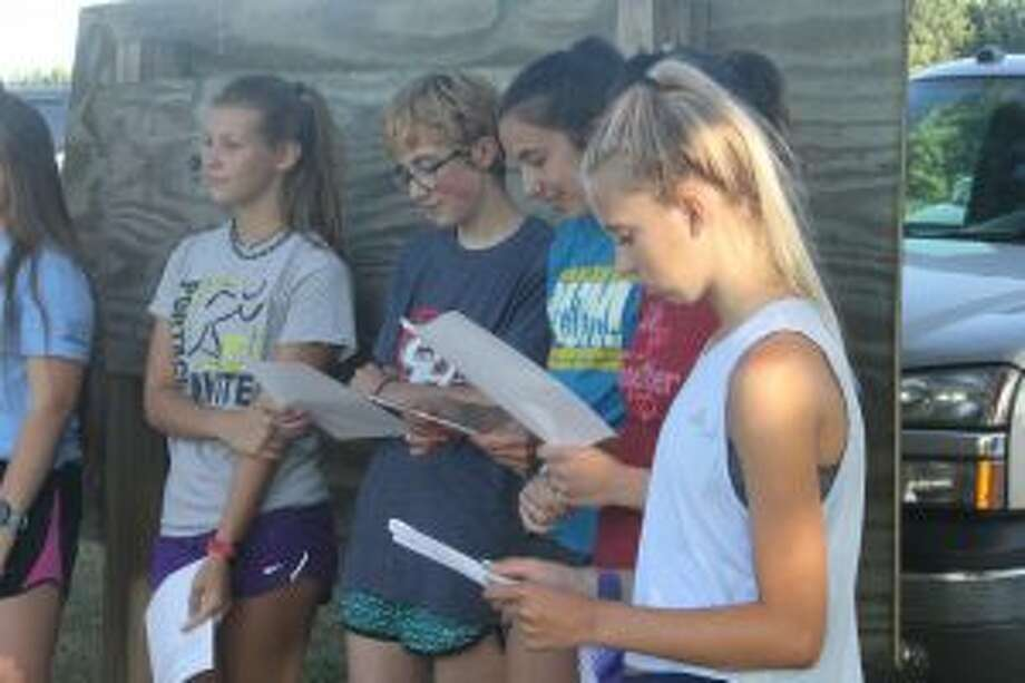 Natalie Newcombe (far right) reads a list of upcoming cross country events last week prior to a Chippewa Hills summer run. (Pioneer photo/John Raffel)