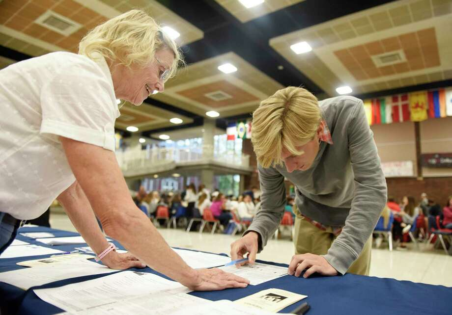 League of Women Voters of Greenwich voter service committee member Barbara Kavanagh helps GHS senior Hayden Sherr sign up to vote at the LWV voting sign-up station at Greenwich High School in Greenwich, Conn. Tuesday, Sept. 25, 2018. The LWV set up a stand in the student center during the lunch periods in an nonpartisan effort to register eligible students to vote in the upcoming election. Photo: Tyler Sizemore / Hearst Connecticut Media / Greenwich Time
