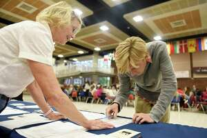 League of Women Voters of Greenwich voter service committee member Barbara Kavanagh helps GHS senior Hayden Sherr sign up to vote at the LWV voting sign-up station at Greenwich High School in Greenwich, Conn. Tuesday, Sept. 25, 2018. The LWV set up a stand in the student center during the lunch periods in an nonpartisan effort to register eligible students to vote in the upcoming election.