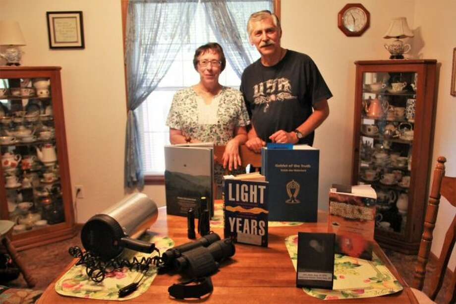 Sally Pleune and Ron Pleune pose with their UFO-communicating equipment. This photo features the light they use to signal UFOs, a pair of binoculars, books on the discussion of UFOs and a photo taken by Ron Pleune during one of his UFO encounters. (Pioneer photo/Alicia Jaimes)
