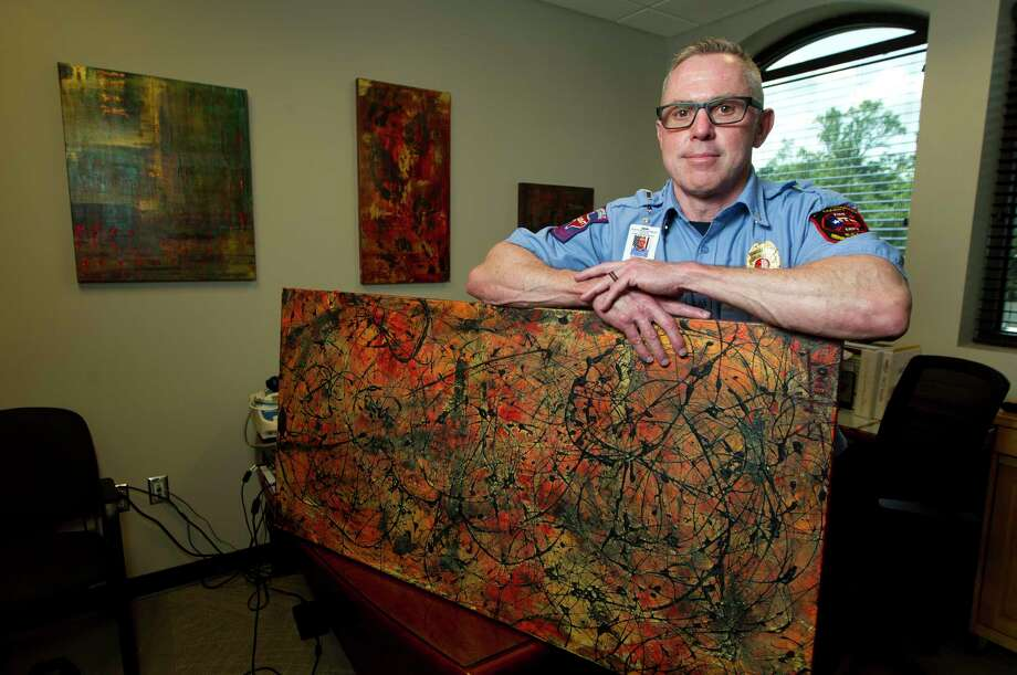 Bobby Hunt, lieutenant of training for the South Montgomery County Fire Department, poses for a portrait with several of his acrylic painting on canvas in Oak Ridge. Hunt has found painting as a creative outlet to help with PTSD. Photo: Jason Fochtman, Houston Chronicle / Staff Photographer / Houston Chronicle