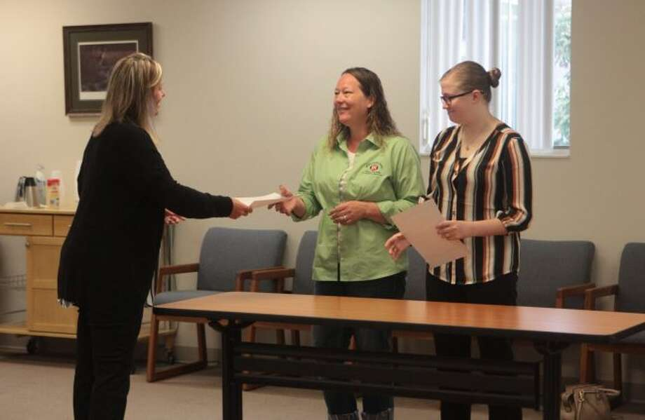 Stacy Shillington (middle) and Kelly Witherspoon (right) were acknowledged by Meceola Central Dispatch Director Megan Erickson (left) for completing their probationary year of training on Monday. (Pioneer photo/Taylor Fussman)