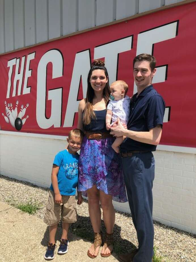 Breanna and Danny Burnett are all smiles as they pose with their two children, 5-year-old Zayden, and 7-month-old Barrett in front of The Gate. The Burnetts said they are looking forward to the updates they hope to bring to the business. (Courtesy photo)