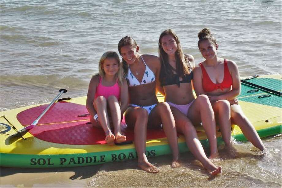 Graeleigh Jensen, of Manistee, prepares to enjoy a paddle boarding adventure with Frankfort National Honor Society members Reagan Thorr, Emily Loney and Cora Scott. (Robert Myers/Pioneer News Network)