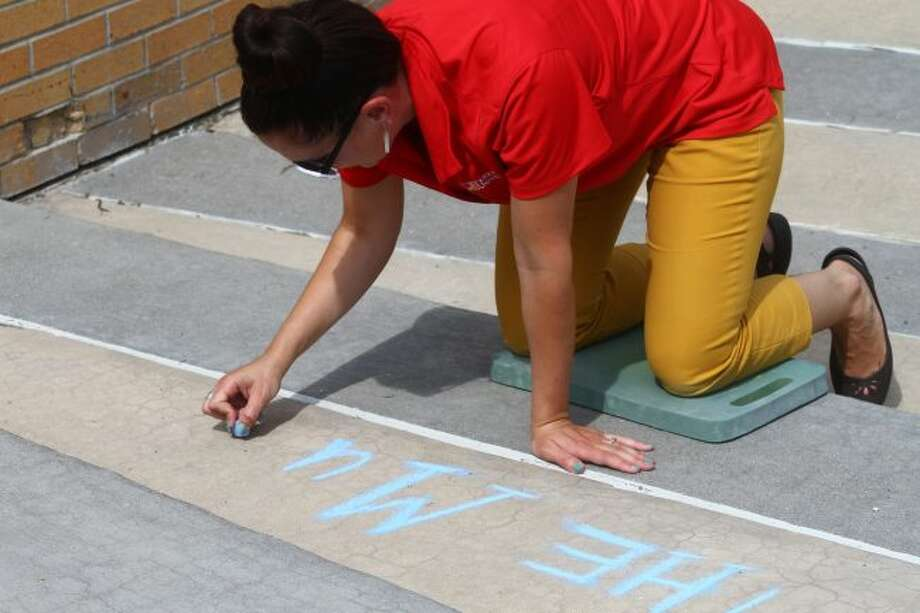 Maggie Walcott chalks a welcoming message into the sidewalk for FSU students. They are returning Thursday, Aug. 22 and Friday Aug. 23. (Pioneer photo/ Catherine Sweeney)