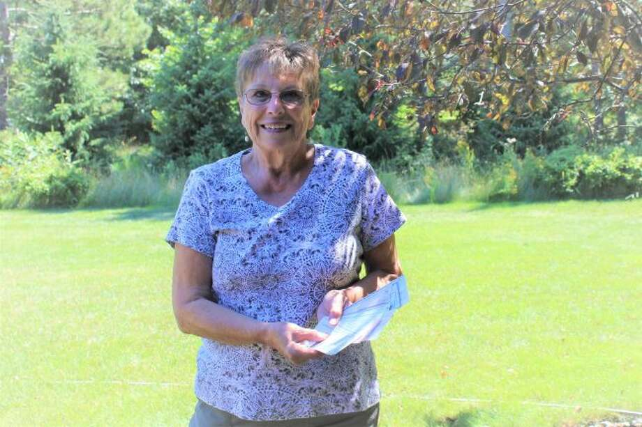 Sheryl Guenthardt, a member of 100 Women Who Care Manistee County, and a volunteer with Blessings in a Backpack accepts checks from 68 Manistee County women in support of the program that helps to feed children on weekends during the school year. (Courtesy photo)