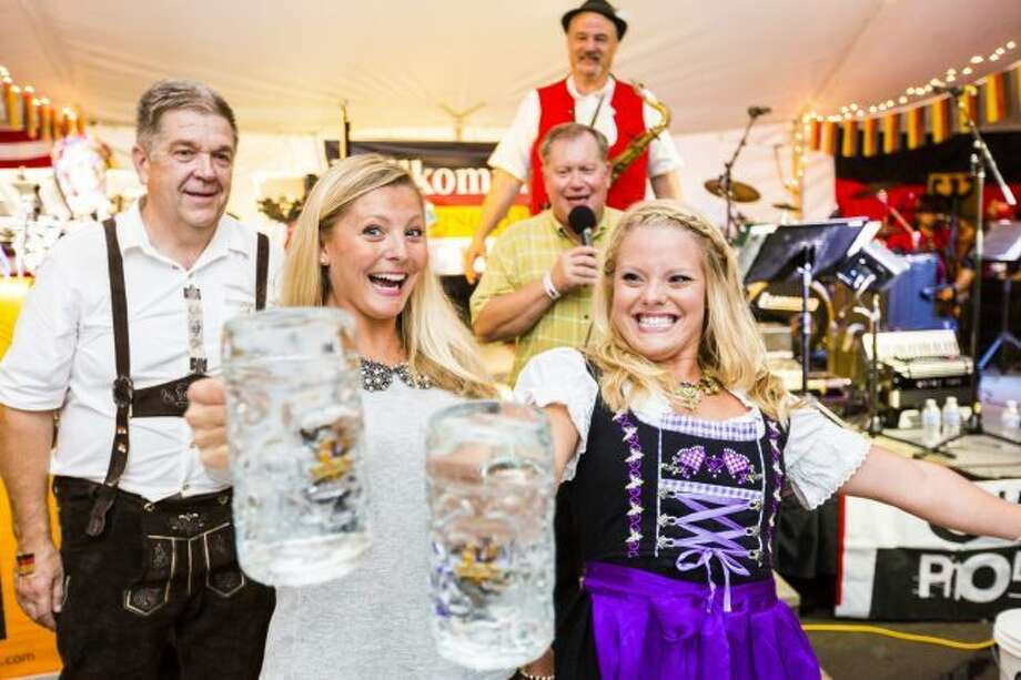 As well as music and food, guests will have the opportunity to play German games. Featured are two women battling it out in a game of masskrugstemmen, holding one liter glass mugs at arms length to see who can hold it the longest. (Pioneer file photo)
