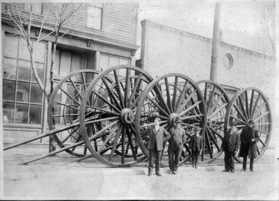 A group poses in front of pairs of logging wheels near the Overpack factory on Pine Street circa 1890.