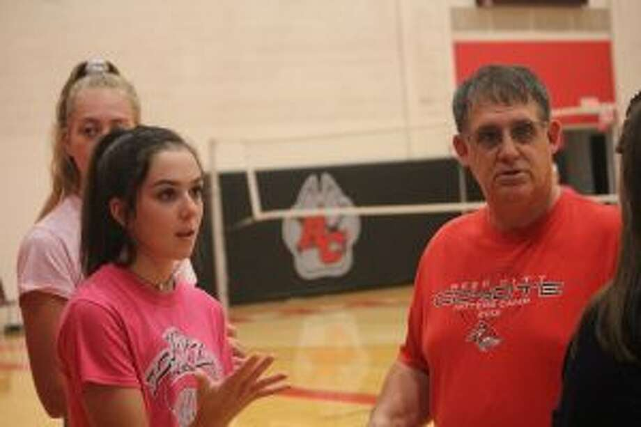 Demi Lodholtz and Don Patterson talk to a player during a Reed CIty practice/