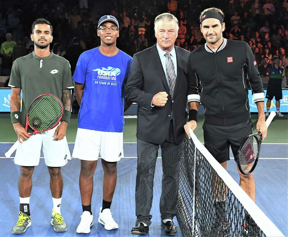 Danbury High School junior Sammy Justo, left centr, with actor Alex Baldwin after tossing the opening coin in Arthur Ashe Stadium on Aug. 26, 2019, before the match between Roger Federer, right, and Sumit Nagal, left. Photo: Garrett Ellwood / USTA / Contributed Photo / 2019 USTA