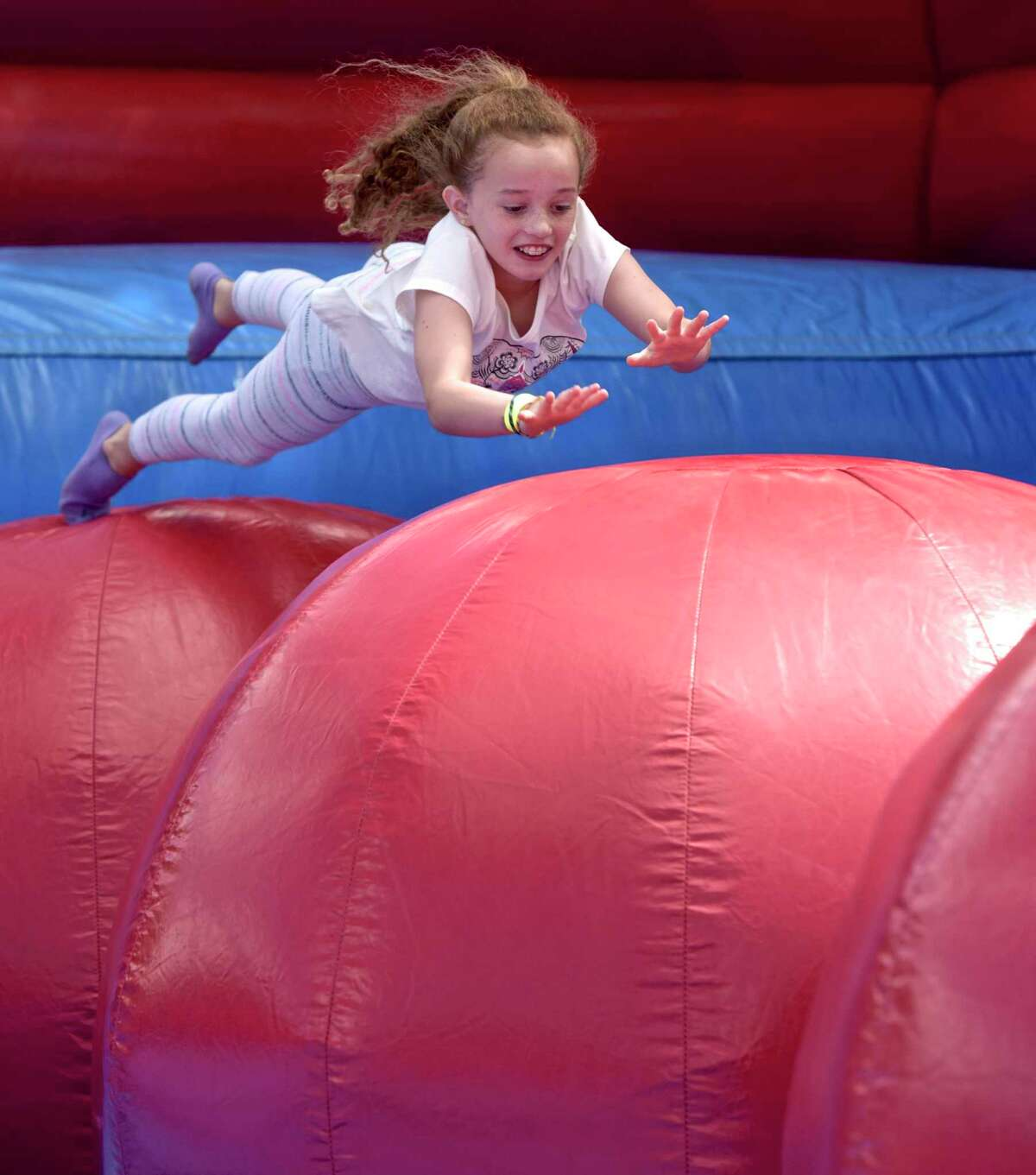 """Mia Johnston, 9, of New Fairfield, jumps across inflated ball on the """"Leaps & Bounds"""" at the Scotty Fund Bethel Town Picnic on Saturday, September 9, 2017, on the Bethel Conn municipal center front lawn."""