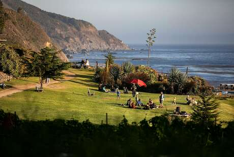 Guests relax on the lawn in front of the lodge as the sun begins to set in the late afternoon at Esalen on Friday, August 30, 2019 in Big Sur, Calif.